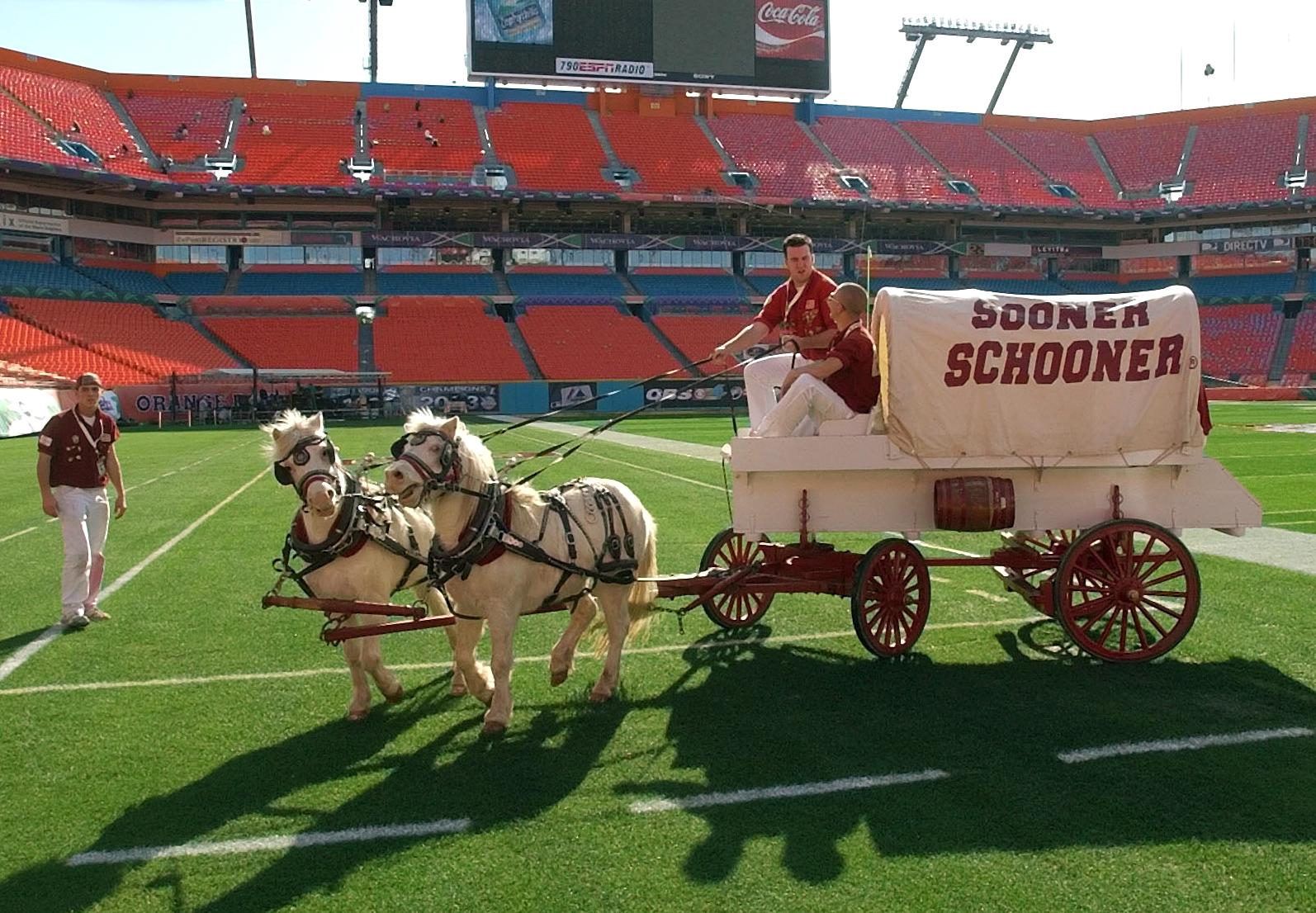 Dos caballos tirando una carreta cubierta en el campo de un estadio (© AP Images)
