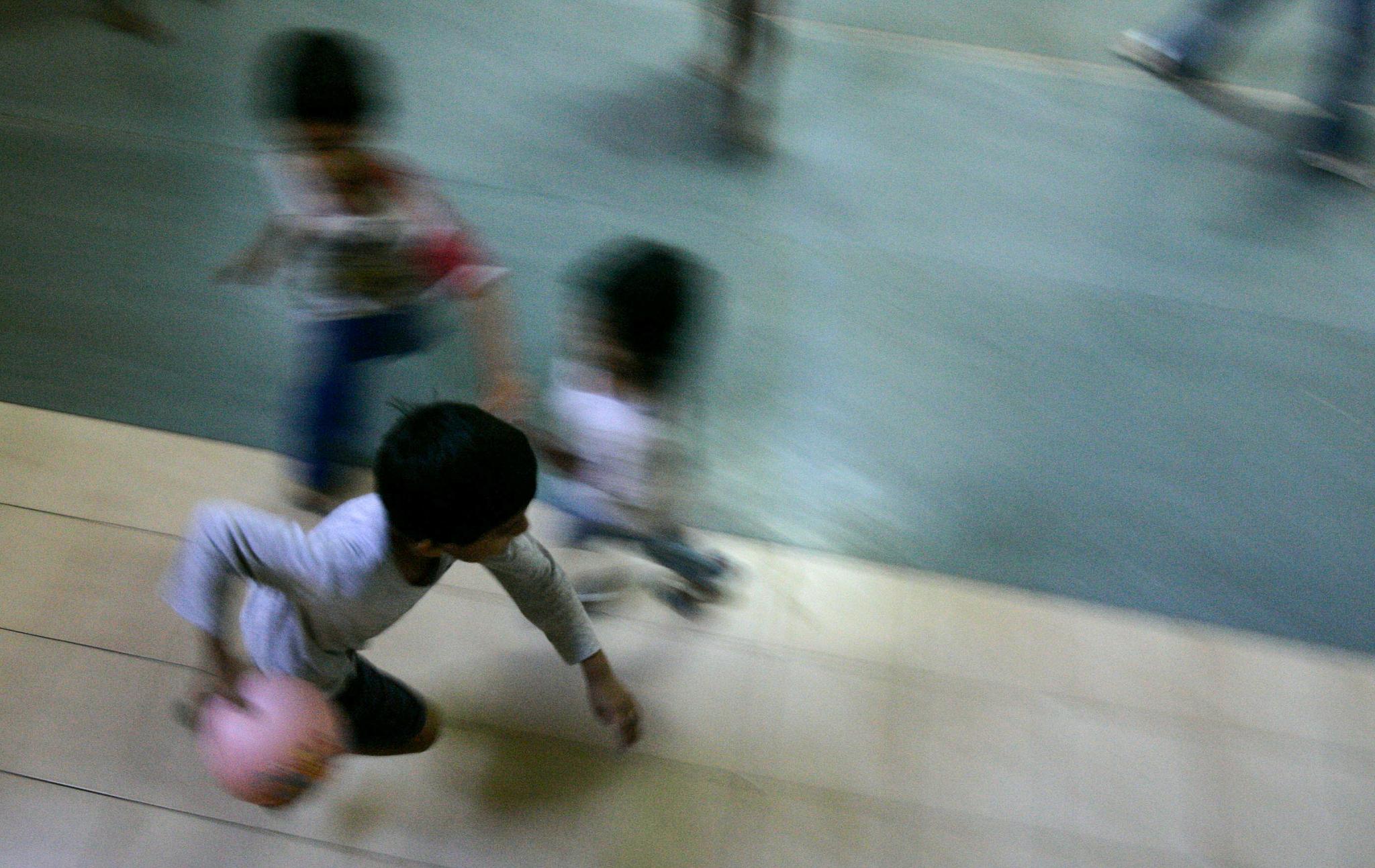 Foto borrosa de niños jugando con una pelota (© AP Images)