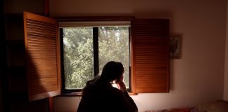 View from behind of woman sitting on bed, looking out window (© AP Images)