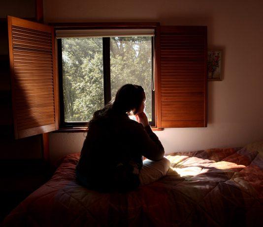 نمایی از پشت سر از زنی که روی تختخواب نشسته و از پنجره بیرون را نگاه می کند. (عکس از آسوشیتدپرس