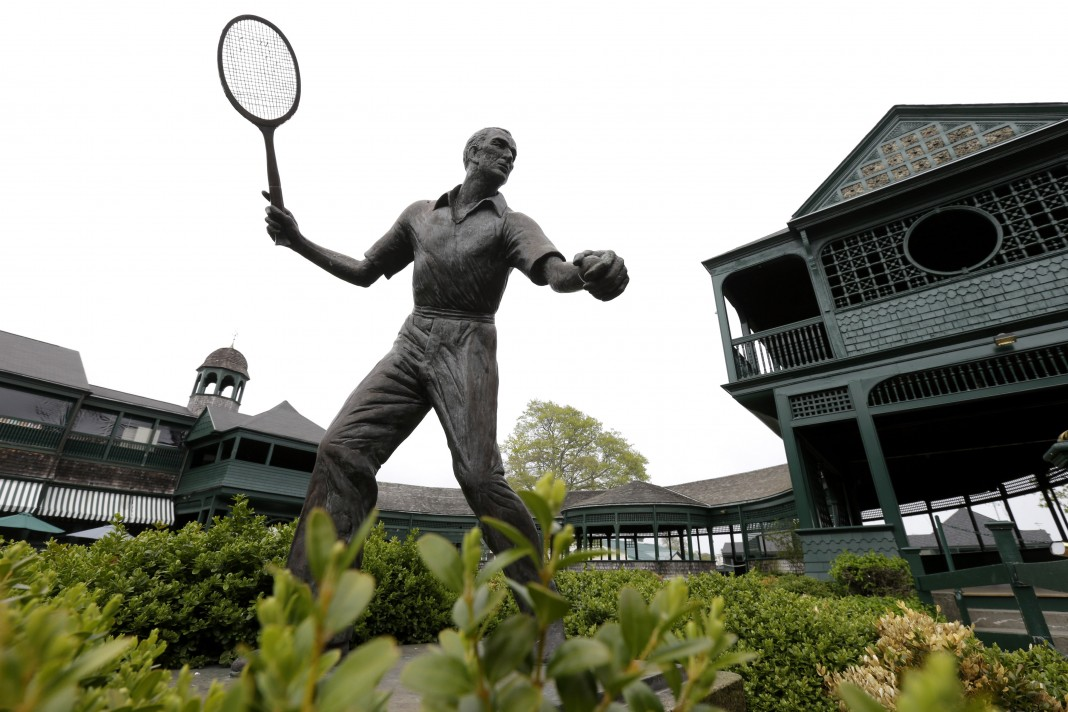 Bronze statue outdoors of tennis player with raised racquet (© AP Images)