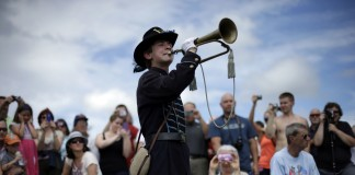 People watching as a boy plays a horn (© AP Images)