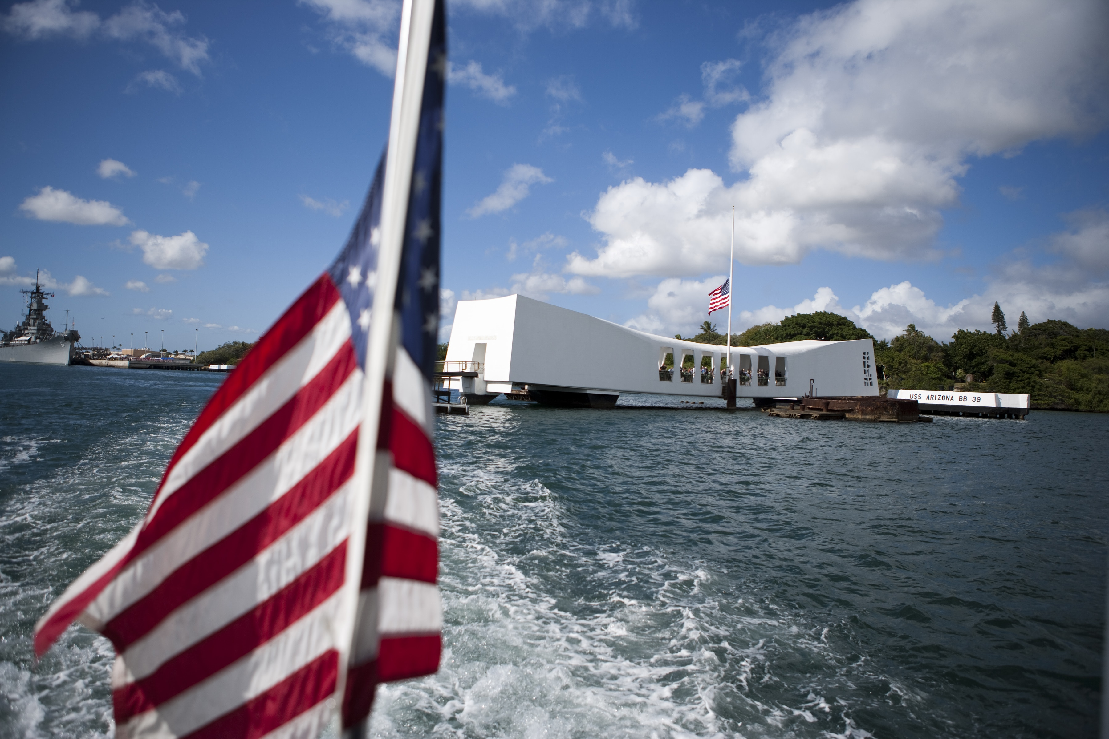 Flag in foreground on boat cruising away from memorial (© AP Images)