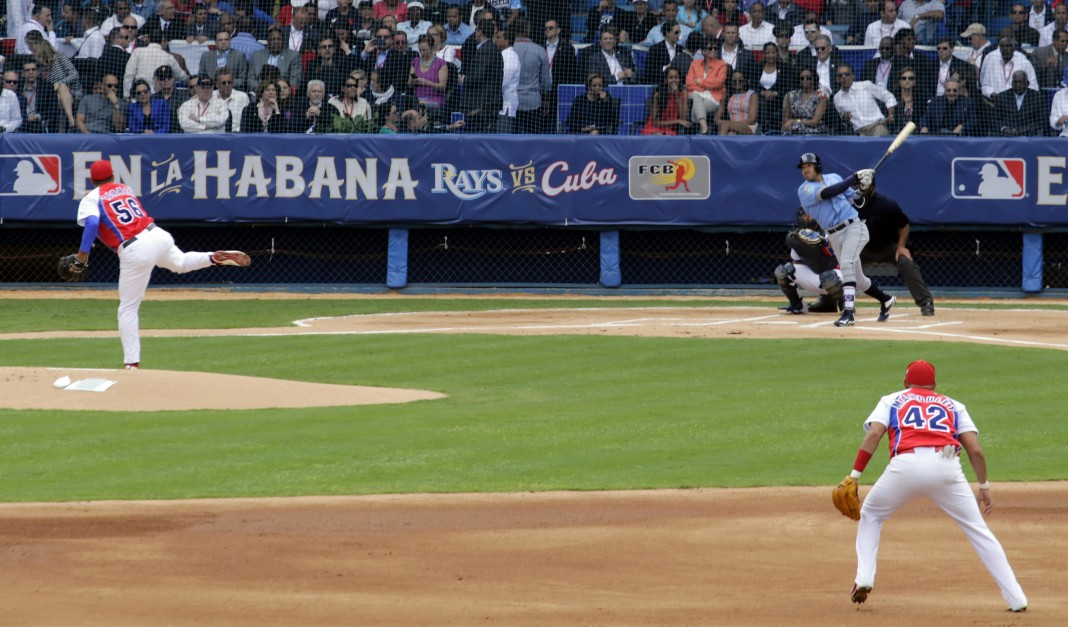 The Obamas, Raúl Castro and others overlooking people on baseball field (© AP Images)