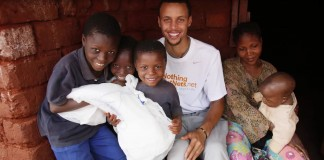 Basketball star Stephen Curry with a family in Tanzania