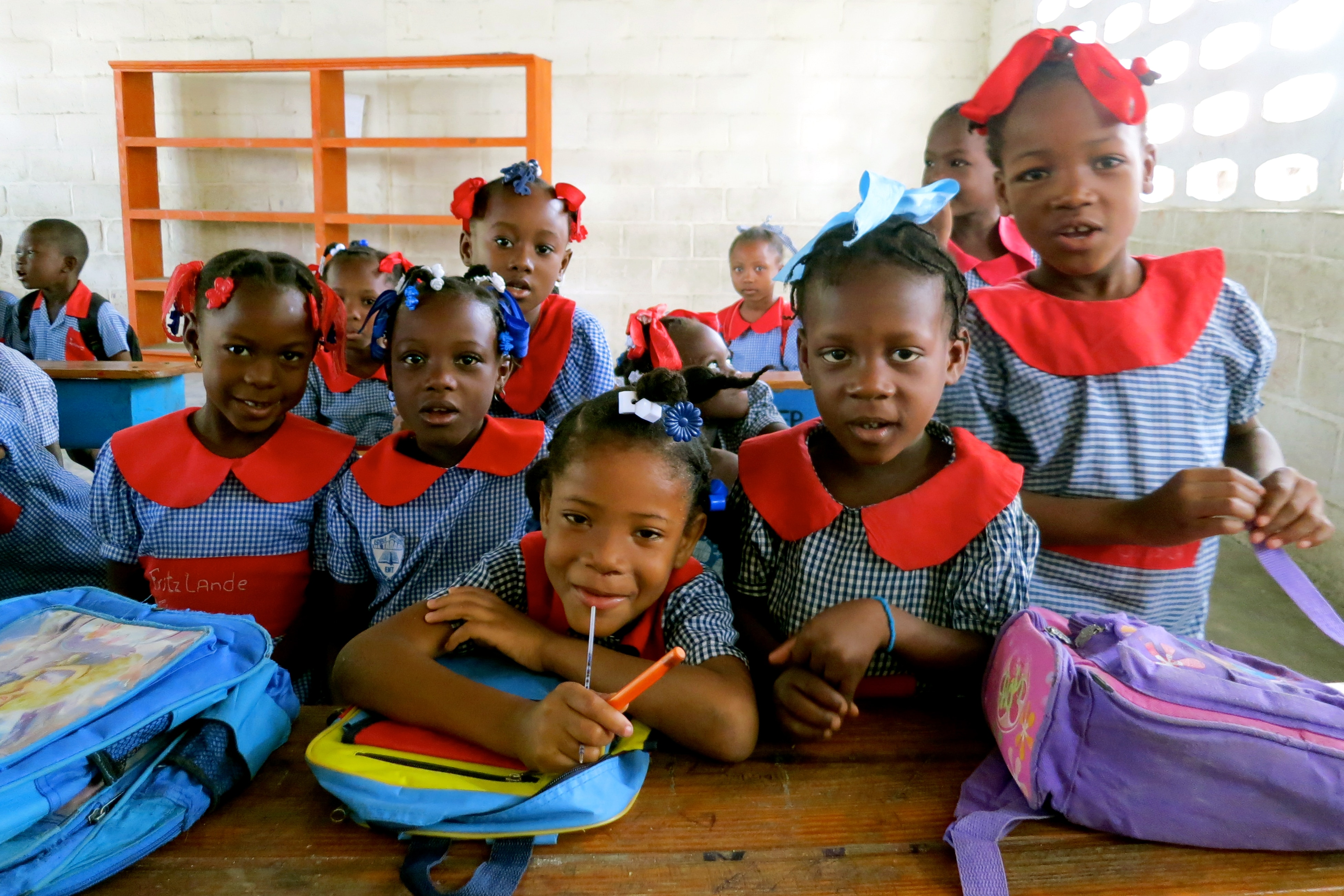 Group of young girls in school uniforms, with backpacks, facing camera (USAID)