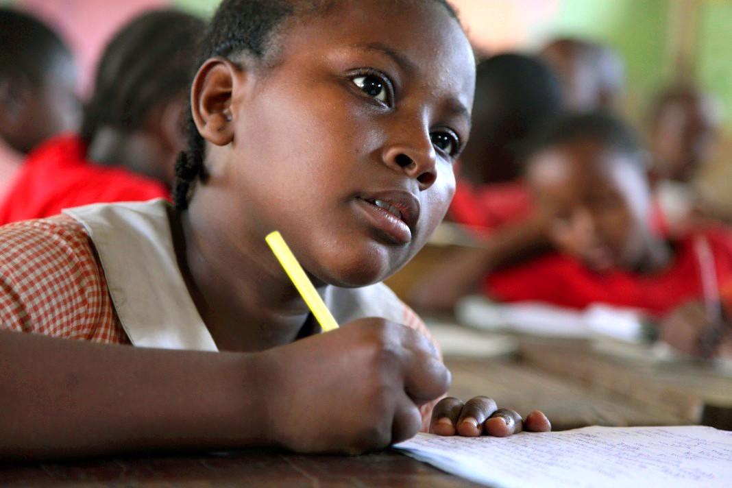 دختر مدرسه ای که با دفترچه یادداشت و مداد پشت میز نشسته است (آژانس توسعه بین المللی ایالات متحده)