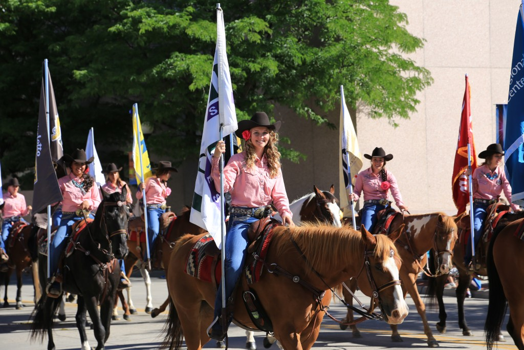Young women holding flags and riding horses (Courtesy of Cheyenne Frontier Days)
