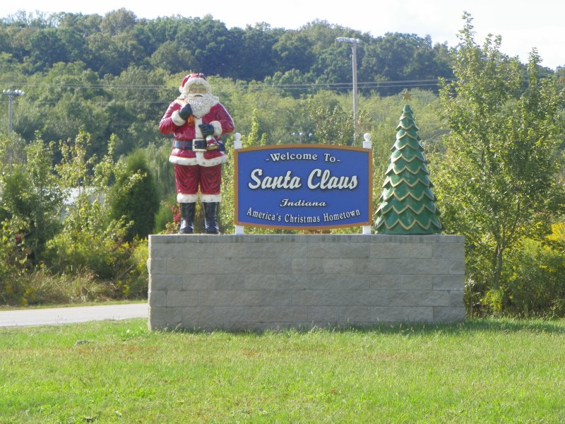 Santa Claus statue and Christmas tree near welcome sign outdoors (Sarah Afshar/Creative Commons)