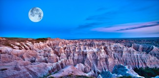 Craggy canyon illuminated by the moon at dusk, with a deepening blue sky above (Shutterstock)