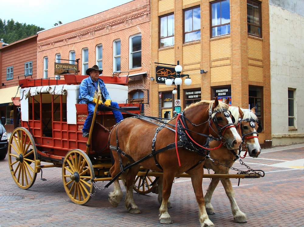 A horse-drawn stagecoach rolls through Deadwood; two-story brick buildings in background (Shutterstock)