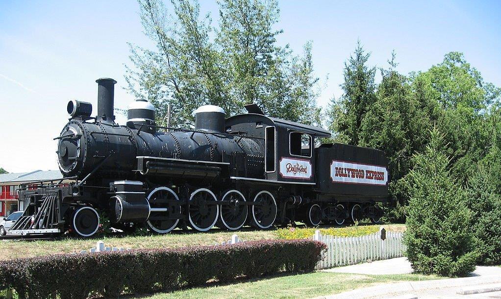 """Una locomotora de vapor de color negro estacionada con un rótulo que dice """"Dollywood"""" (Sdenny123/Creative Commons)"""