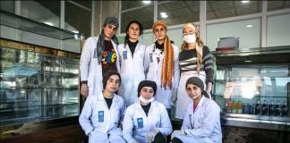 身穿白色工作服的妇女站在面包店食品柜前(UNDP)