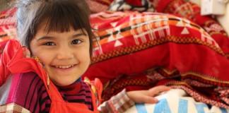 Une fillette souriante, la main sur un sac du Programme alimentaire mondial (Programme alimentaire mondial/Mohammed Al Bahbahani)