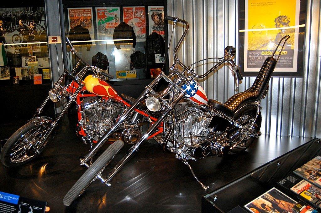 دو موتورسیکلت در موزه به نمایش گذاشته شده اند و پوسترهایی نیز در پس زمینه دیده می شوند. (Danemroberts/Creative Commons)