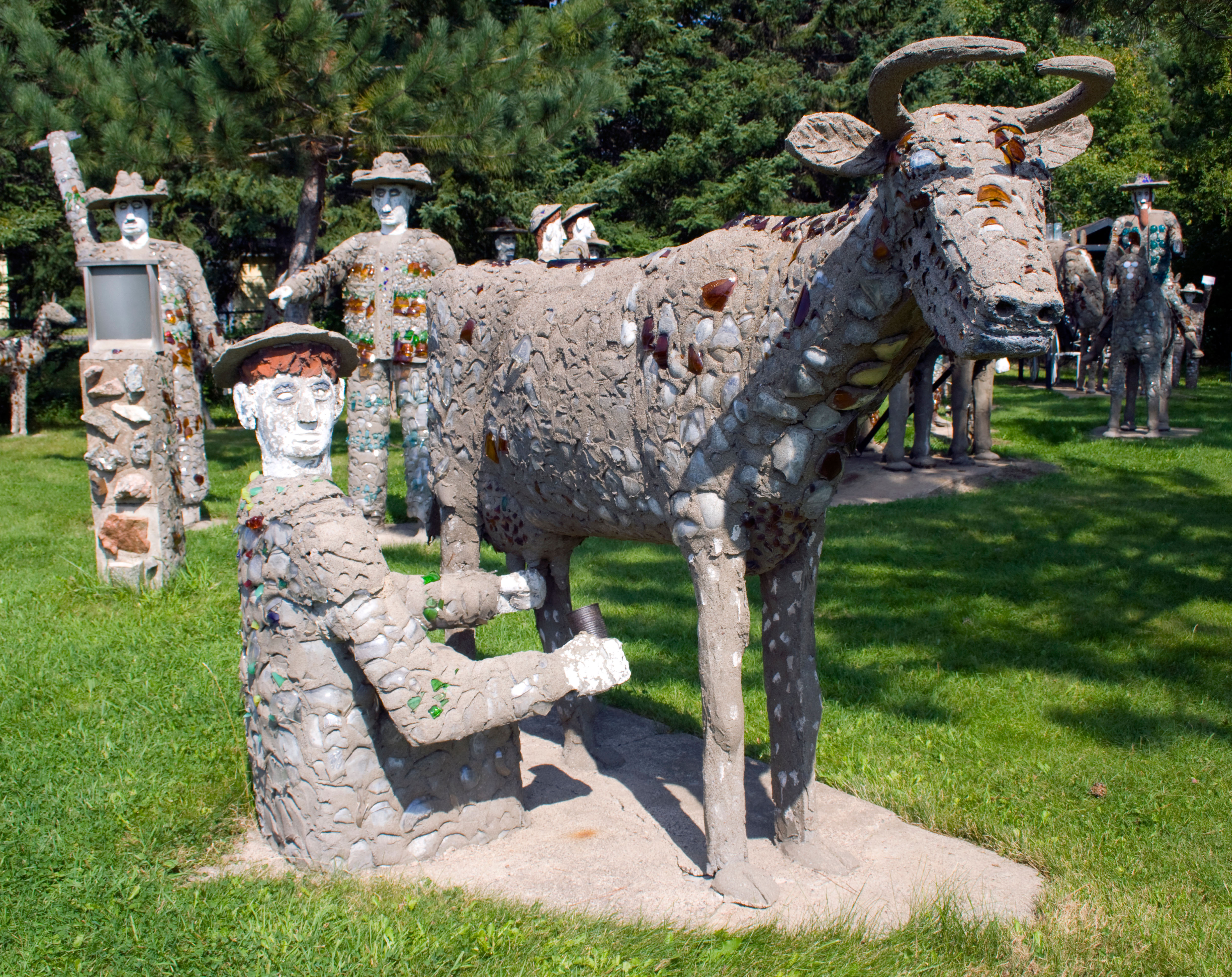 Folk-art concrete sculpture of a farmer milking a cow; other concrete statues in background (© Franck Fotos/Alamy Stock Photo)