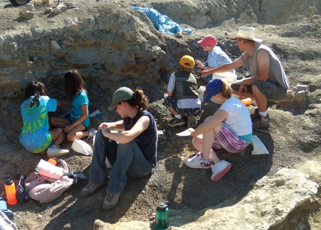 Paleontologist and six youths digging on hill (Courtesy of the Wyoming Dinosaur Center)