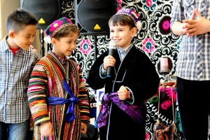 Young boys standing on a stage, one holding a microphone (Courtesy of the Tajik American Cultural Association)