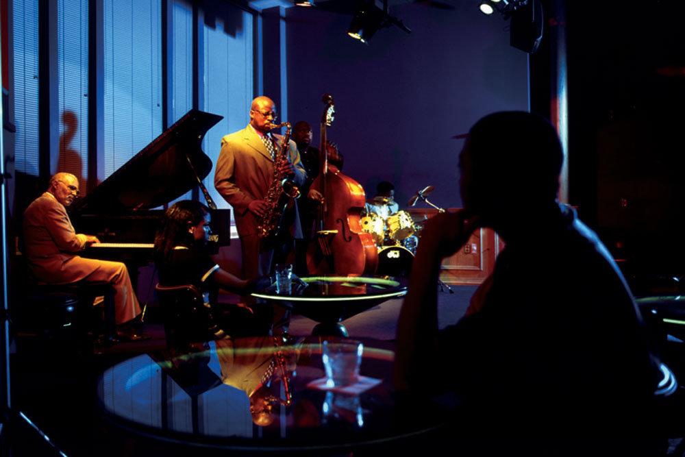 نوازندگان سازهای پیانو، ساکسافون، و گیتار بیس روی صحنه یک باشگاه شبانه (عکس تقدیمی از موزه جاز آمریکا)