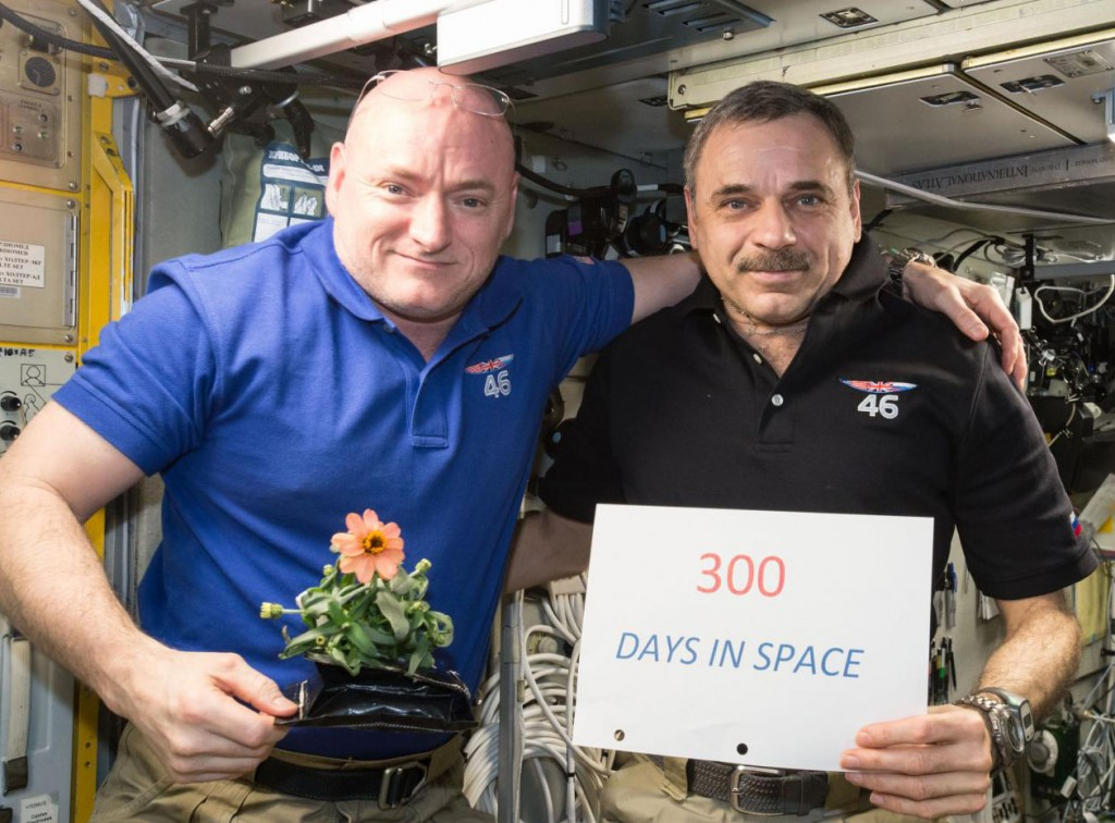 Astronaut Scott Kelly and cosmonaut Mikhail Kornienko posing, with Kelly holding a flower and Kornienko a sign (NASA)