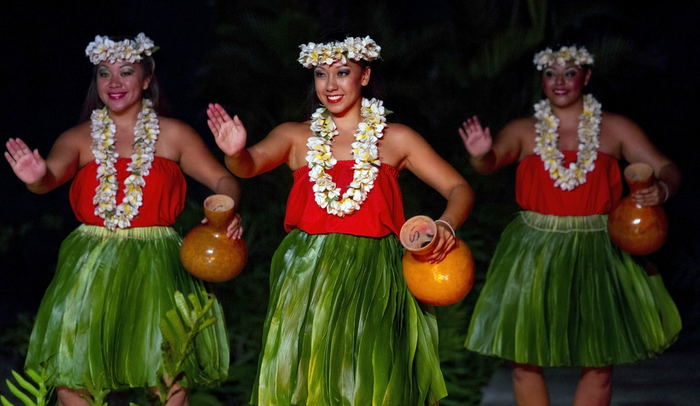 Three women dressed in hula attire, holding jugs and dancing (Shutterstock)