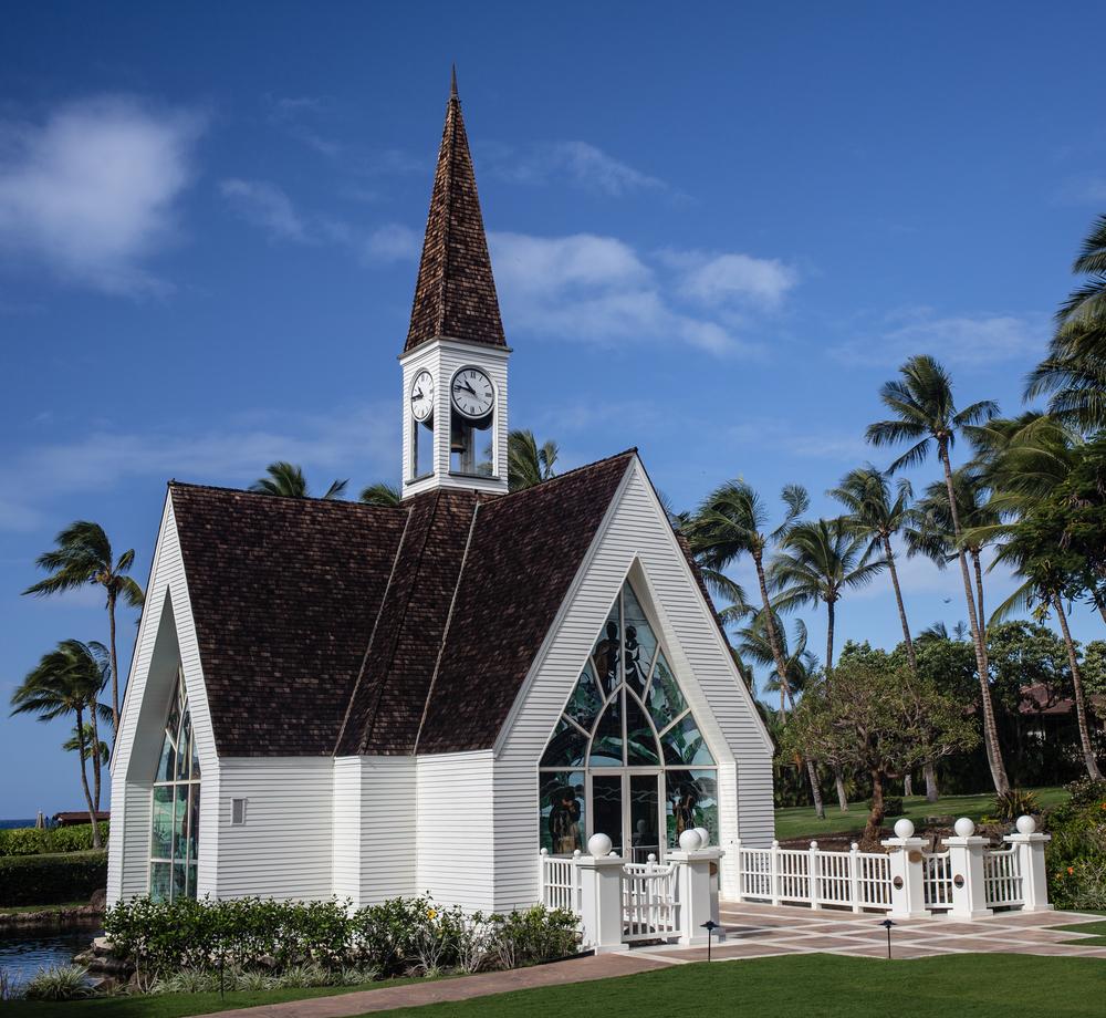White wedding chapel sitting near palm trees (Shutterstock)