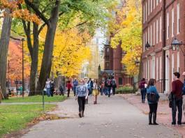 Woman walking down sidewalk on a college campus (Shutterstock)