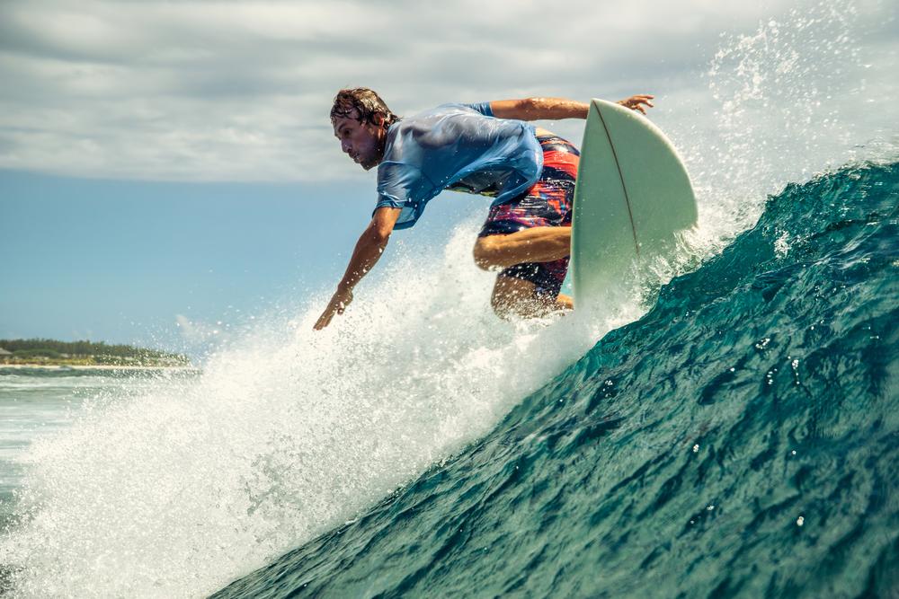 Surfer riding wave (Shutterstock)