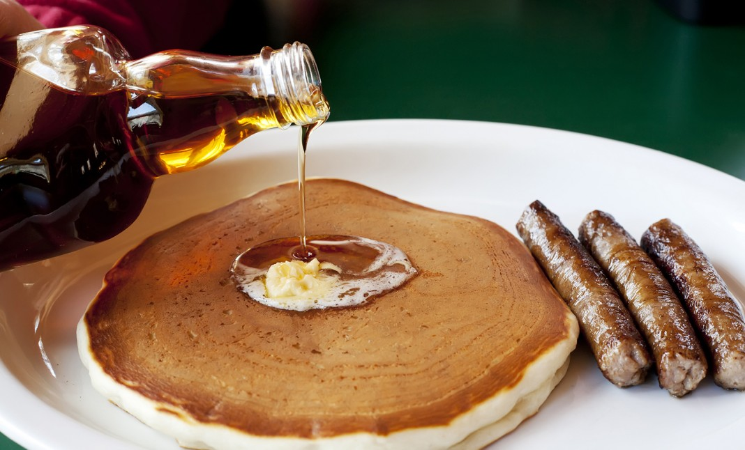Syrup being poured over a stack of pancakes (Shutterstock)