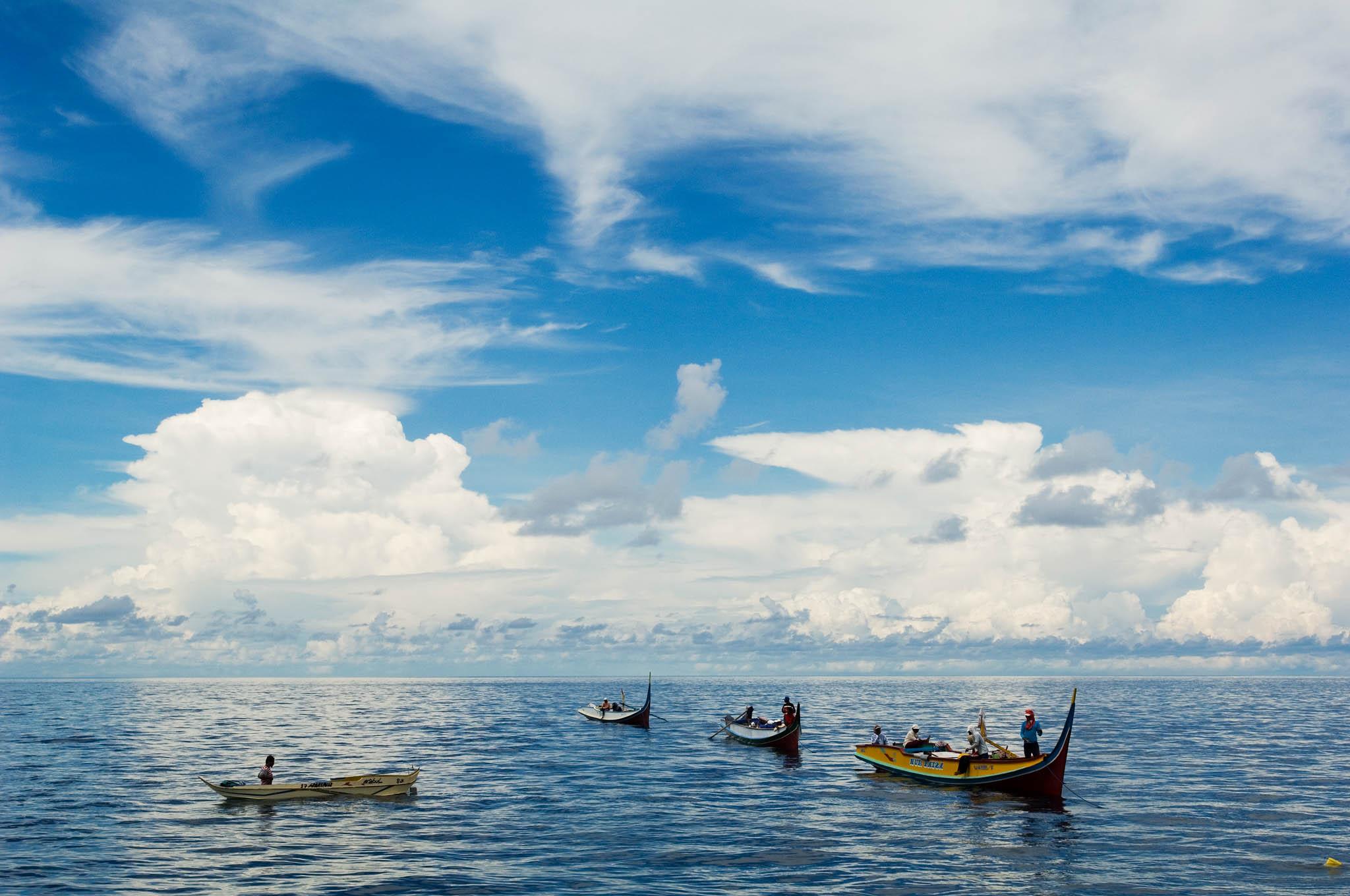 Men riding small boats on sea (© National Geographic Creative/Mauricio Handler)