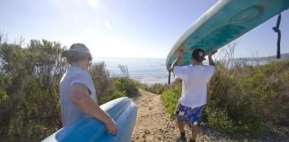 دو مرد جوان در ساحل در حال حمل تخته های موج سواری هستند (عکس های آسوشیتد پرس)