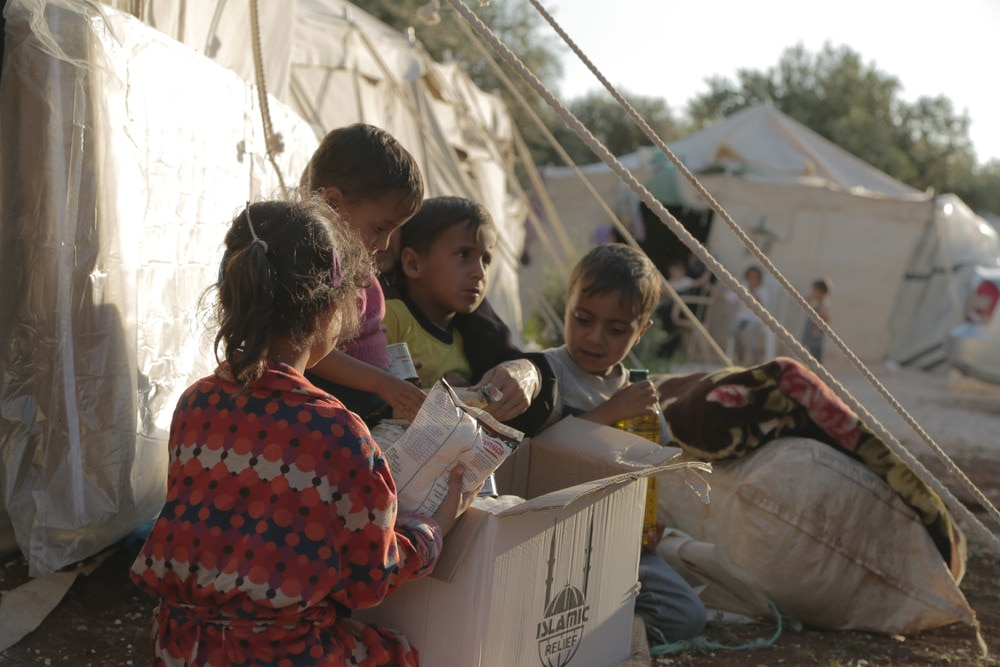 Children opening box outside tent (Courtesy of Islamic Relief USA)