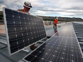 Workmen installing solar panels on building rooftop (U.S. Department of Energy)