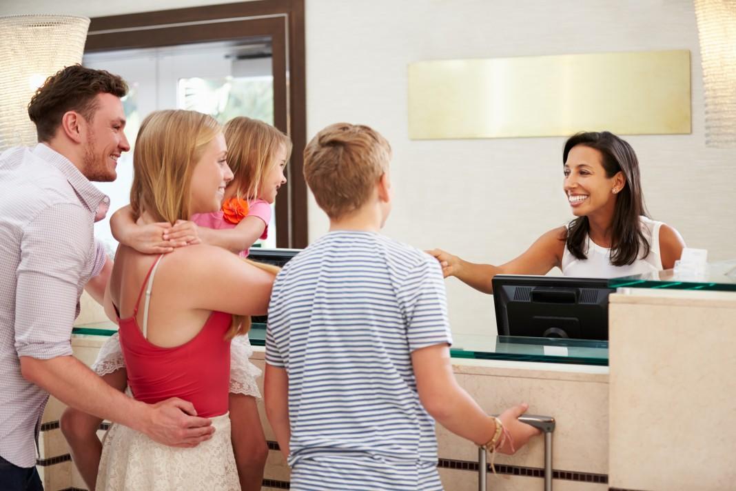 Family standing at desk talking to clerk (© AP Images)