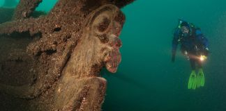 Scuba diver swimming near shipwreck's figurehead in Lake Michigan (© AP Images)