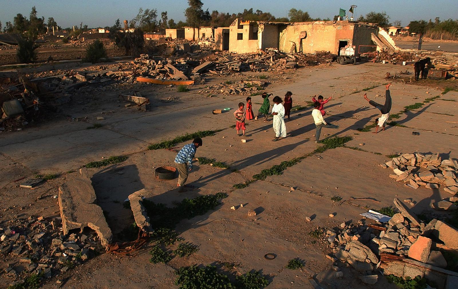 Crianças brincando em torno de escombros de edifício em terreno danificado (© AP Images)