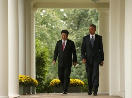 Xi Jinping and President Obama walking between rows of columns (© AP Images)