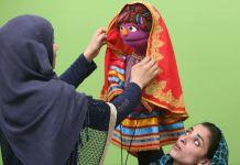 شخصی در حال تنظیم کردن روسری یک عروسک (عکس از آسوشیتدپرس)