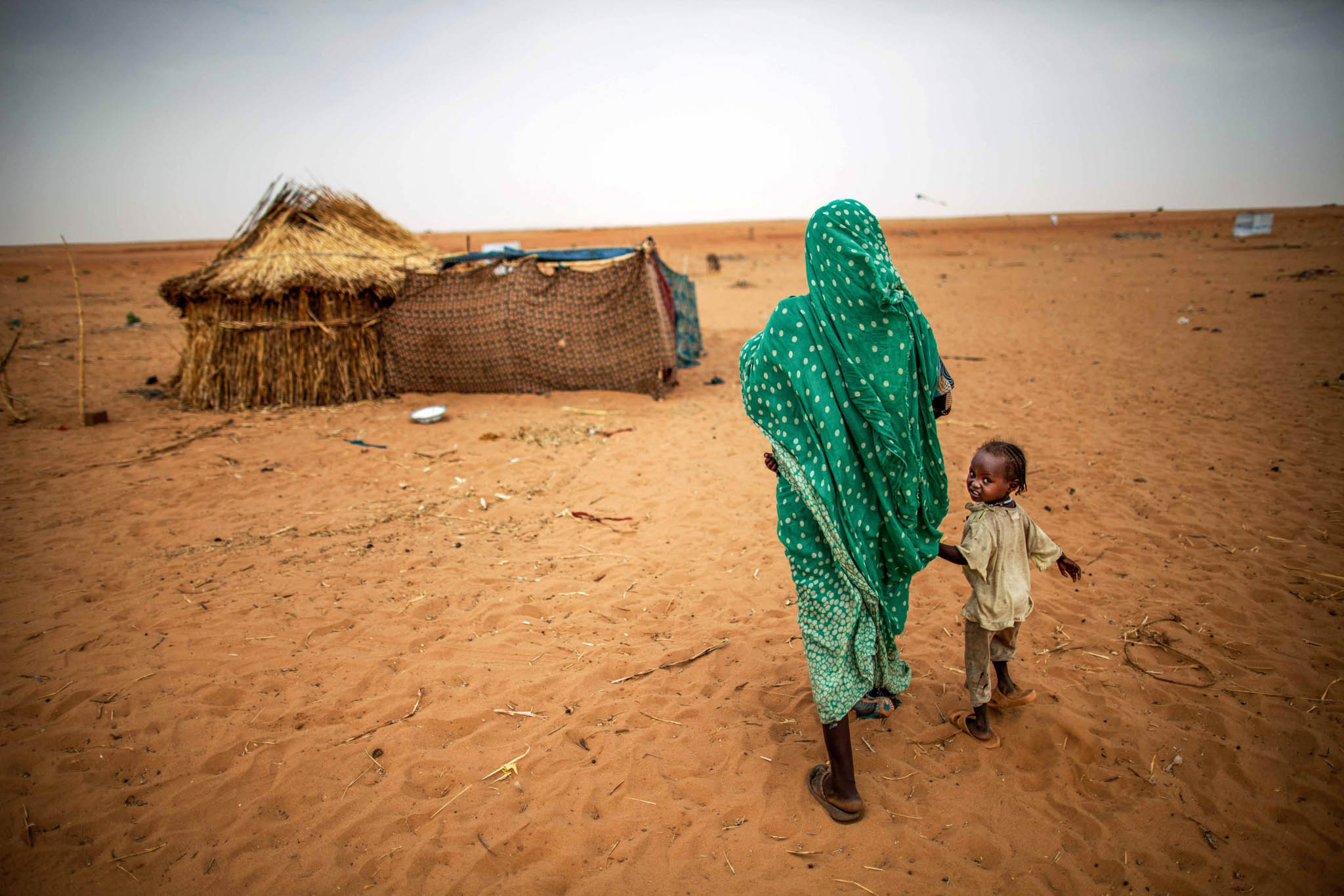 Refugee woman and child walking toward makeshift hut in desert camp (© AP Images)