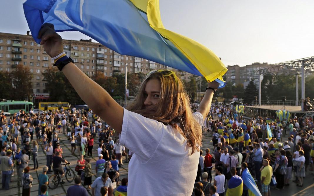Mujer levanta una bandera ucraniana frente a una enorme multitud (© AP Images)