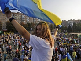 Woman holding Ukrainian flag in front of large crowd (© AP Images)