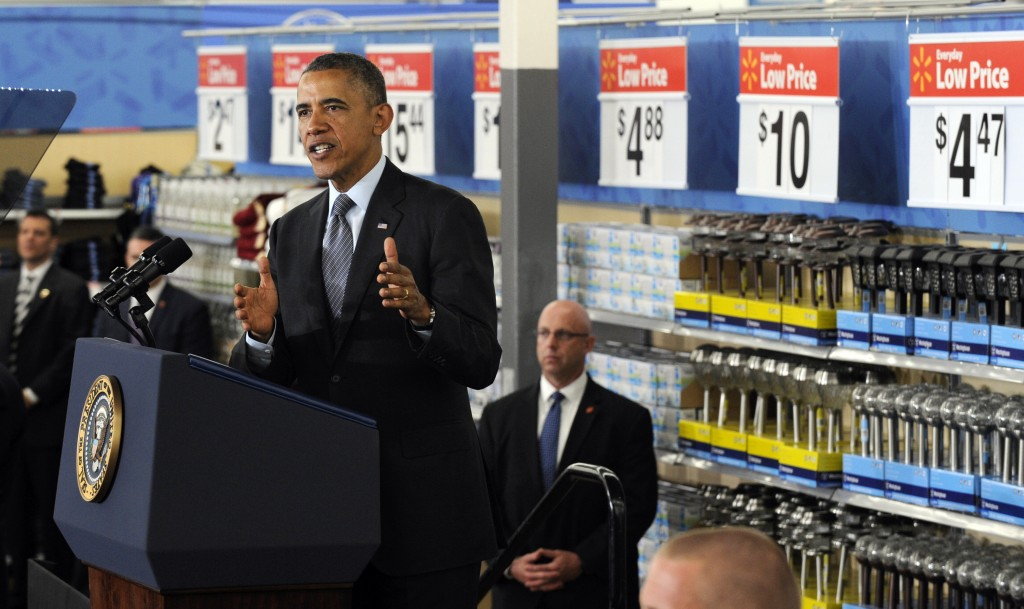 President Obama speaking at podium in large store, against backdrop of shelves of merchandise (© AP Images)