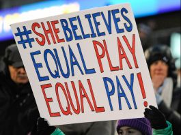 "Girl holding sign reading ""#SheBelieves Equal Play Equal Pay"" (© AP Images)"