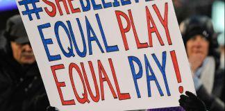 Une fillette tenant une affiche revendiquant l'égalité salariale entre les joueurs de foot des deux sexes (© AP Images)