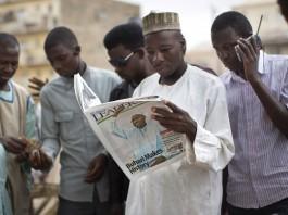 Warga Nigeria membaca koran di Kano, bagian utara Nigeria, pada hari kedua penghitungan suara pemilu 2015. (© AP Images)