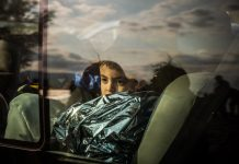 Un garçon assis dans un bus, enveloppé dans une bâche plastique, regardant par la vitre (© AP Images)