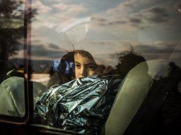 Menino olhando pela janela de um ônibus (© AP Images)