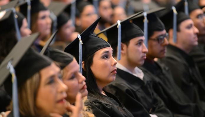 Students wearing caps and gowns sitting in rows (© AP Images)