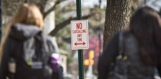 Un panneau dans une rue, et de chaque côté une femme vue de dos (© AP Images)