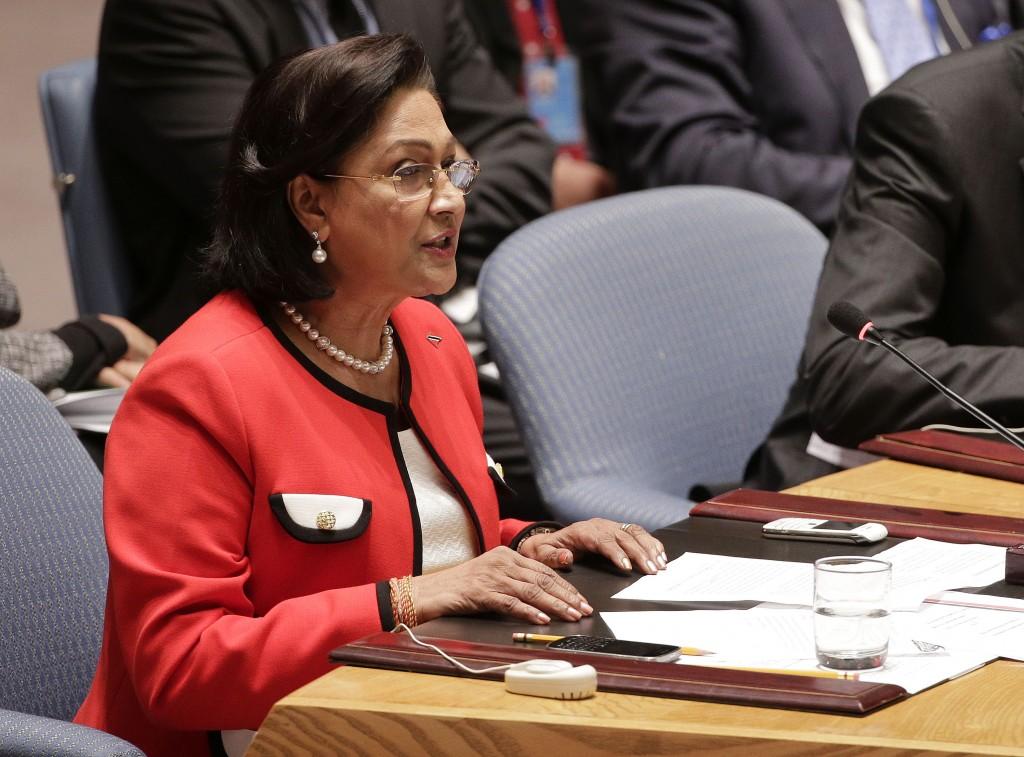 Mantan perdana menteri Trinidad dan Tobago Kamla Persad-Bissessar duduk, berbicara di konferensi (© AP Images)